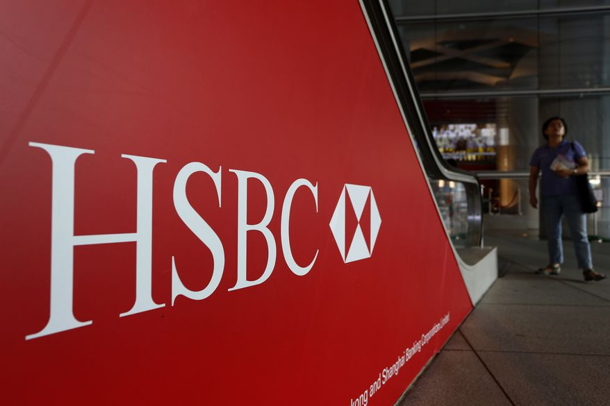 ** FILE ** Pedestrians pass a sign with the HSBC logo in Hong Kong on Monday, July 30, 2012. HSBC, the British banking giant, will pay $1.9 billion to settle a money-laundering probe by federal and state authorities in the United States, a law enforcement official said Monday, Dec. 10, 2012. (AP Photo/Vincent Yu)