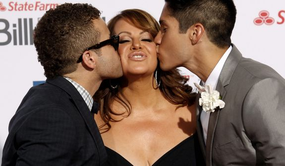 **FILE** Singer Jenni Rivera (center) is kissed by singers Nacho (left) and Chino as they walk the red carpet at the Latin Billboard Awards in Coral Gables, Fla., on April 26, 2012. (Associated Press)