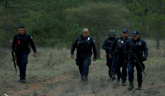 Federal police officers return from the site where a plane carrying U.S-born singer Jenni Rivera crashed near Iturbide, Mexico, on Dec. 9, 2012. (Associated Press)
