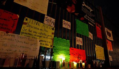 Signs of support, photos and candles that were placed by fans of U.S.-born singer Jenni Rivera stand Dec. 10, 2012, at the gates of the Arena Monterrey in Monterrey, Mexico, where Rivera held her last concert.  (Associated Press)