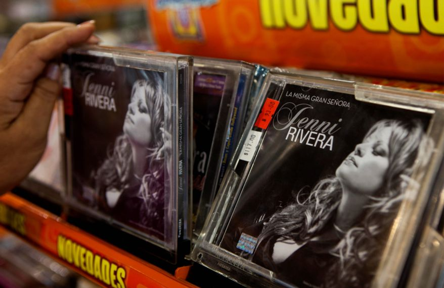 A person takes a CD of singer Jenni Rivera displayed for sale at a music store in Mexico City on Dec. 10, 2012. U.S. authorities confirmed that Rivera, a U.S.-born singer whose soulful voice and openness about her personal troubles made her a Mexican-American superstar, was killed in a Dec. 9 plane crash in northern Mexico. (Associated Press)