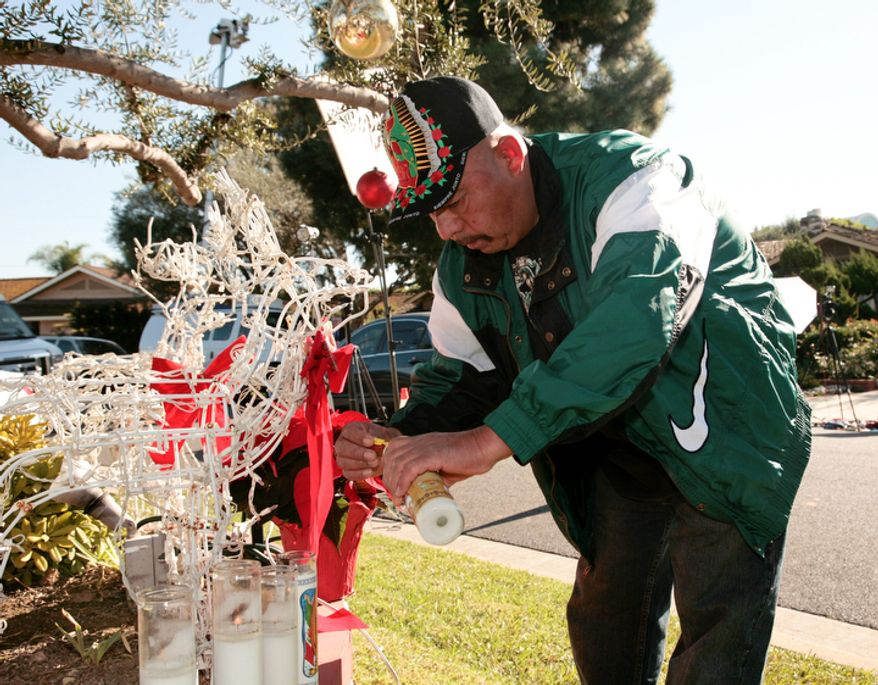 Fan Jose Ruelas lights a candle outside the home of singer Jenni Rivera's mother in Lakewood, Calif., on Dec. 10, 2012. Rivera died the previous day in a plane crash in Mexico. (Associated Press)