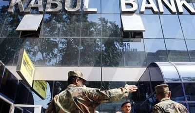 **FILE** Afghan soldiers chat in front of the main office of Kabul Bank in Kabul, Afghanistan, on Sept. 1, 2010. (Associated Press)