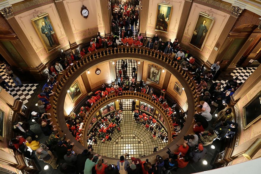 Protesters gather for a rally in the state Capitol Rotunda in Lansing, Mich., on Tuesday, Dec. 11, 2012. The crowd is demonstrating against right-to-work legislation passed last week that would make Michigan the 24th state with a right-to-work law. Rules required a five-day wait before the House and Senate vote on each other's bills; lawmakers are scheduled to reconvene Tuesday, and Gov. Rick Snyder has pledged to sign the bills into law. (AP Photo/Paul Sancya)