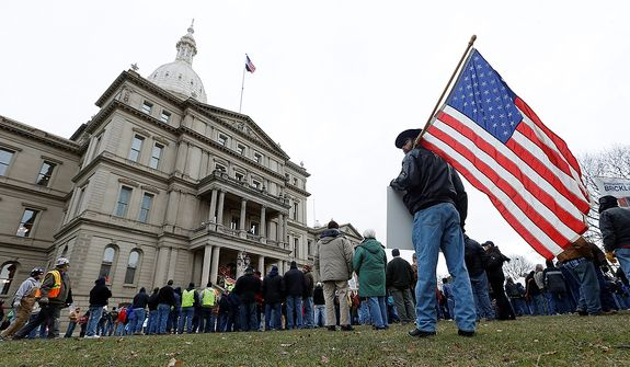 A protester holds an American flag at a rally on the state Capitol grounds in Lansing, Mich., on Tuesday, Dec. 11, 2012. The crowd is demonstrating against legislation that would make Michigan the 24th state with a right-to-work law. (AP Photo/Paul Sancya)