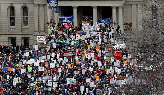 Protesters gather for a rally at the state Capitol in Lansing, Mich., on Tuesday, Dec. 11, 2012. The crowd is demonstrating against legislation that would make Michigan the 24th state with a right-to-work law. (AP Photo/Paul Sancya)