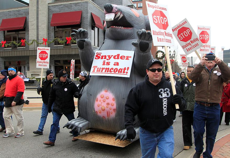 Sheet-metal workers from Toledo, Ohio, escort an inflatable rat during a march to the state Capitol grounds in Lansing, Mich., on Tuesday, Dec. 11, 2012. The crowd is demonstrating against legislation that would make Michigan the 24th state with a right-to-work law. (AP Photo/Carlos Osorio)