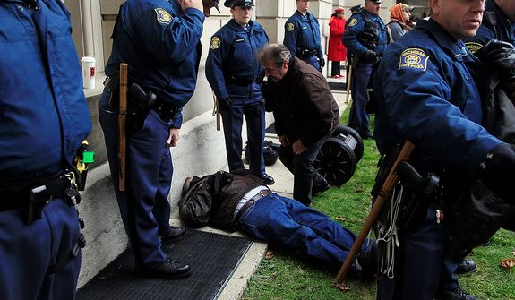 Michigan State Police surround a man who was allegedly knocked off his segway scooter by a sheriff deputy on horseback during a rally on the State Capitol grounds in Lansing, Mich., Tuesday, Dec. 11, 2012. The crowd is protesting right-to-work legislation that was passed by the state legislature last week. (AP Photo/Carlos Osorio)