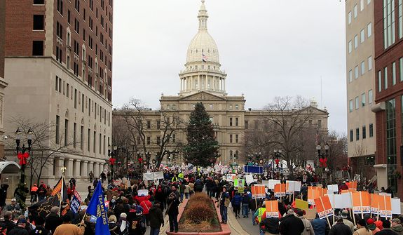 Thousands of supporter march to the State Capitol grounds in Lansing, Mich., Tuesday, Dec. 11, 2012. The crowd is protesting right-to-work legislation that was passed by the state legislature last week.  (AP Photo/Carlos Osorio)