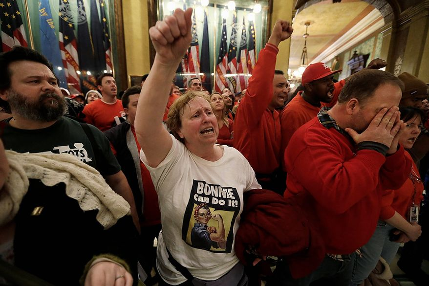Protesters gather for a rally in the rotunda at the State Capitol in Lansing, Mich., Tuesday, Dec. 11, 2012. The crowd is protesting right-to-work legislation passed last week. Michigan could become the 24th state with a right-to-work law next week. Rules required a five-day wait before the House and Senate vote on each other's bills; lawmakers are scheduled to reconvene Tuesday and Gov. Snyder has pledged to sign the bills into law. (AP Photo/Paul Sancya)