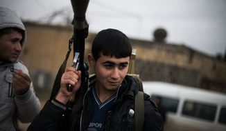 A Free Syrian Army fighter holds his weapon as he prepares himself for advance, close to a military base, near Azaz, Syria, on Dec. 10, 2012. The gains by rebel forces came as the European Union denounced the Syrian conflict, which activists say has killed more than 40,000 people. (Associated Press)
