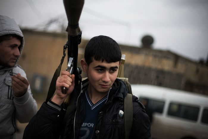 A Free Syrian Army fighter holds his weapon as he prepares himself for advance, close to a military base, near Azaz, Syria, on Dec. 10, 2012. The gains by rebel forces came as the European Union denounced the Syrian conflict, which acti