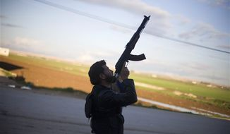 A Free Syrian Army fighter points his weapon as he watches a Syrian Army jet, not pictured, in Fafeen village, north of Aleppo province, Syria, Tuesday, Dec. 11, 2012. (AP Photo/Manu Brabo)
