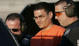 **FILE** Convicted terrorism plotter Jose Padilla (center) is escorted to a waiting police vehicle by federal marshals near downtown Miami on Jan. 5, 2006. (Associated Press)