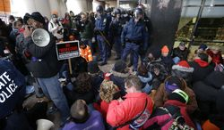 Protesters sit during a rally at the George W. Romney State Building, where Gov. Snyder has an office in Lansing, Mich., Tuesday, Dec. 11, 2012. The crowd is protesting right-to-work legislation passed last week. Michigan could become the 24th state with a right-to-work law next week. Rules required a five-day wait before the House and Senate vote on each other's bills; lawmakers are scheduled to reconvene Tuesday and Gov. Snyder has pledged to sign the bills into law. (AP Photo/Paul Sancya)