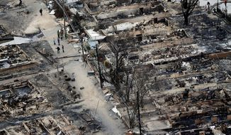** FILE ** An aerial view shows burned-out homes in the Breezy Point section of the Queens borough of New York on Tuesday, Oct. 30, 2012. The tiny beachfront neighborhood, told to evacuate before Superstorm Sandy hit New York, burned down as it was inundated by floodwaters, transforming a quaint corner of the Rockaways into a smoke-filled debris field. (AP Photo/Mike Groll)