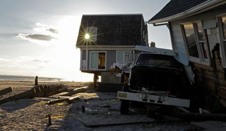 A man strolls along the sand as a burst of sunlight passes through the window of a beachfront house badly damaged in Superstorm Sandy in the Belle Harbor section of the Queens borough of New York on Wednesday, Dec. 5, 2012. (AP Photo/Kathy Willens)