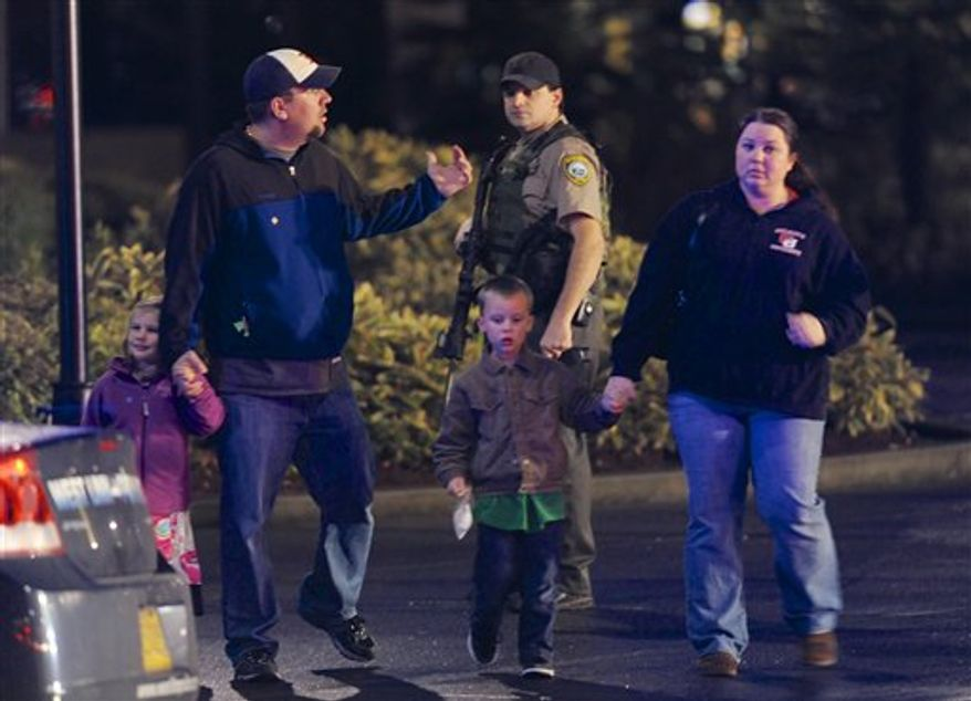 A family leaves the scene of a multiple shooting at Clackamas Town Center Mall in Clackamas, Ore., Tuesday Dec. 11, 2012. A gunman is dead after opening fire in the Portland, Ore., area shopping mall Tuesday, killing two people and wounding another, sheriff's deputies said. (AP Photo/Greg Wahl-Stephens)