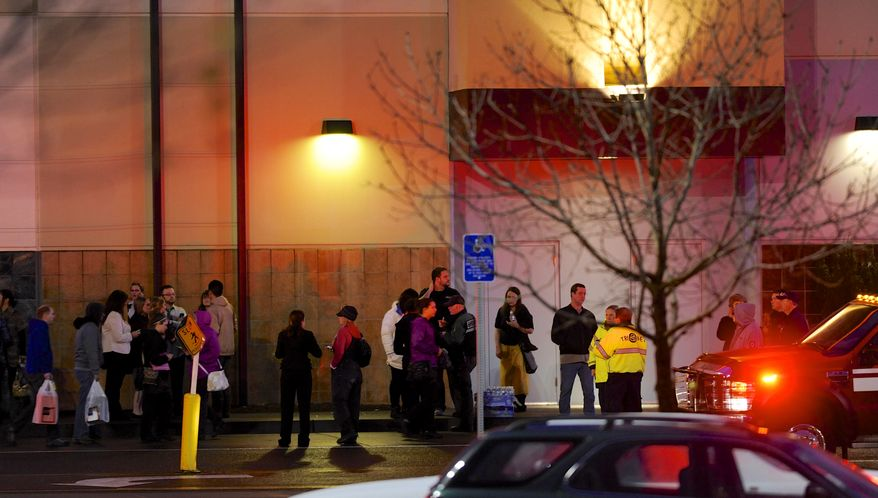 Shoppers wait to be evacuated outside the scene of a multiple shooting at Clackamas Town Center Mall in Clackamas, Ore., Tuesday Dec. 11, 2012. A gunman is dead after opening fire in the Portland, Ore., area shopping mall Tuesday, killing two people and wounding another, sheriff's deputies said. (AP Photo/Greg Wahl-Stephens)
