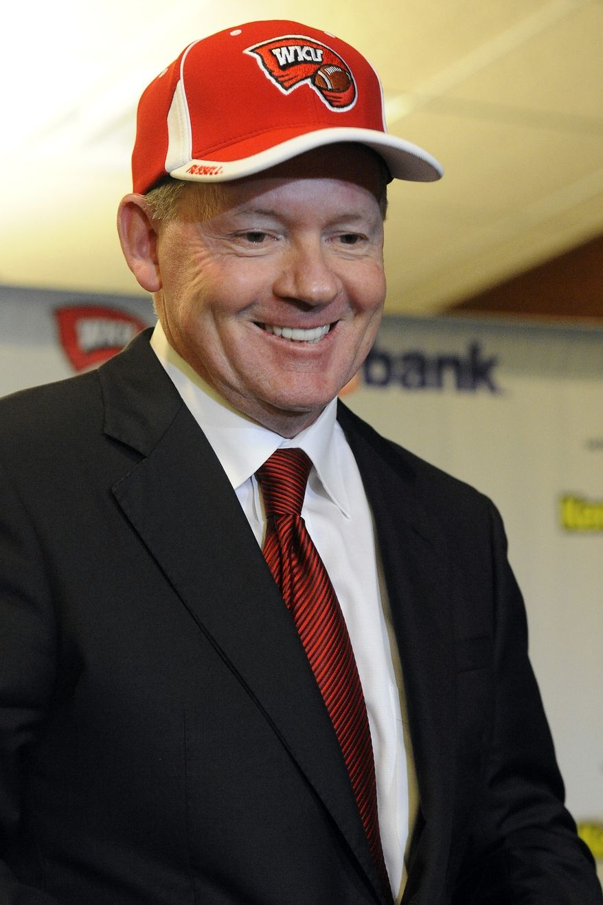 """New Western Kentucky head coach Bobby Petrino smiles during an NCAA college football news conference, Monday, Dec. 10, 2012, in Bowling Green, Ky. The 51-year-old was fired by Arkansas in April for a """"pattern of misleading"""" behavior following an accident in which the coach was injured while riding a motorcycle with his mistress as a passenger but now wants to make the most of his second chance. (AP Photo/The Daily News, Joe Imel)"""