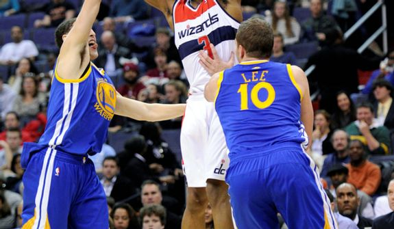 Washington Wizards guard Bradley Beal (3) passes the ball against Golden State Warriors guard Klay Thompson (11) and David Lee (10) during the second half of the Warriors' 101-97 win on Dec. 8, 2012, in Washington. (Associated Press)