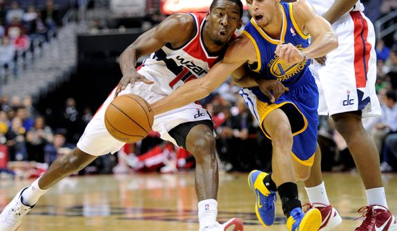 Golden State Warriors guard Stephen Curry (right) tries to get the ball away from Washington Wizards guard Jordan Crawford (left) during the second half of the Warriors' 101-97 win on Dec. 8, 2012, in Washington. (Associated Press)