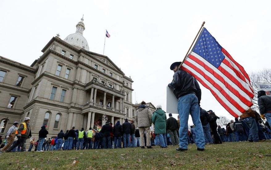 A protester holds an American flag at a rally on the State Capitol grounds in Lansing, Mich., Tuesday, Dec. 11, 2012. The crowd is protesting right-to-work legislation passed last week. (AP Photo/Paul Sancya)