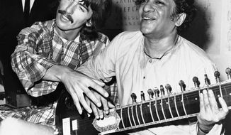 Ravi Shankar shows George Harrison of the Beatles how to play the sitar in Los Angeles in August 1967. Mr. Shankar, the father of singer Norah Jones of the Little Willies, died Tuesday at 92. (Associated Press)