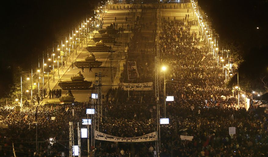 Egyptian army tanks (left) deploy as protesters gather outside the presidential palace during a demonstration against President Mohammed Morsi in Cairo on Tuesday, Dec. 11, 2012. Thousands of opponents and supporters of Egypt's Islamist president staged rival rallies in the nation's capital Tuesday, four days ahead a nationwide referendum on a contentious draft constitution. (AP Photo/Hassan Ammar)