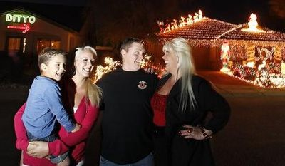 "Kristina Green (right), her daughter Breanah Gray (second left) and grandson Cameron Gray (left) laugh together with neighbor Eric Cyr on Dec. 11, 2012,as they pose in front of their homes in Maricopa, Ariz. Green could not compete with Cyr's 20,000 Christmas lights on his home, so she has put up a 450 light display that says ""DITTO"" with an arrow pointing to Cyr's home. (Associated Press)"