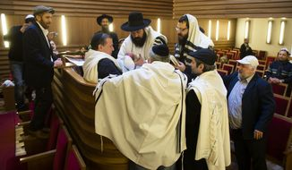** FILE ** Rabbi Yacov Gassinovitch (center), a mohel, is surround by other rabbis and relatives as he holds 8-day-old Jonathan during the boy's circumcision at synagogue in Berlin on Oct. 29, 2012. (Associated Press)