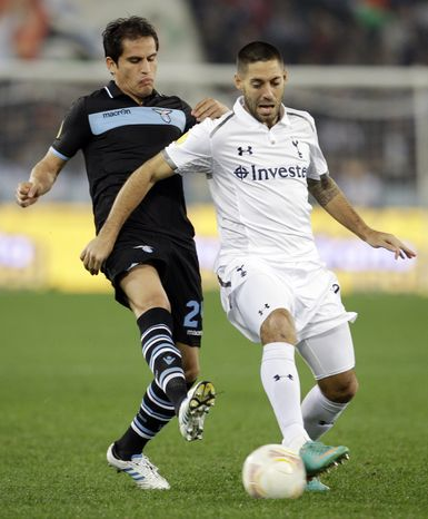 Lazio midfielder Cristian Ledesma, left, and Tottenham Hotspur's Clint Dempsey fight for the ball during an Europa League Group J soccer match at Rome's Olympic stadium, Thursday, Nov. 22, 2012. (AP Photo/Andrew Medichini)