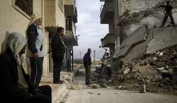 Syrian men use sledgehammers to break the concrete and search for belongings under the rubble of a residential building in Maaret Misreen, near Idlib, Syria, that was destroyed in a government airstrike on Dec. 12, 2012. (Associated Press)