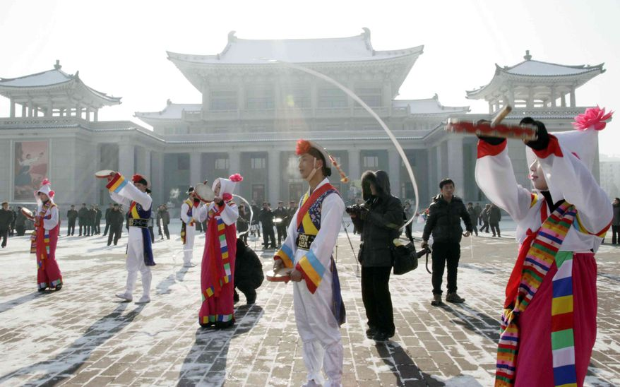 North Korean youths in traditional Korean outfit play instruments in front of the Pyongyang Grand Theatre in Pyongyang, North Korea, to celebrate a rocket launch on Wednesday, Dec. 12, 2012. (AP Photo/Jon Chol Jin)