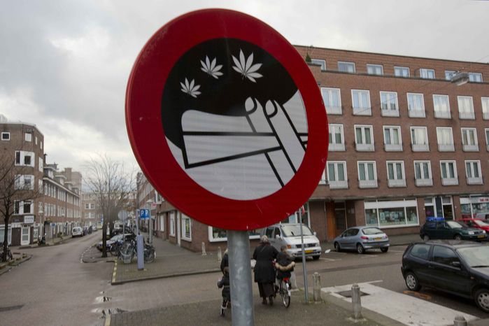 Mothers and their children leave a nearby school as a sign prohibiting the use of marijuana in a designated area is seen in Amsterdam, Wednesday, Dec. 12, 2012. (AP Photo/Peter Dejong)
