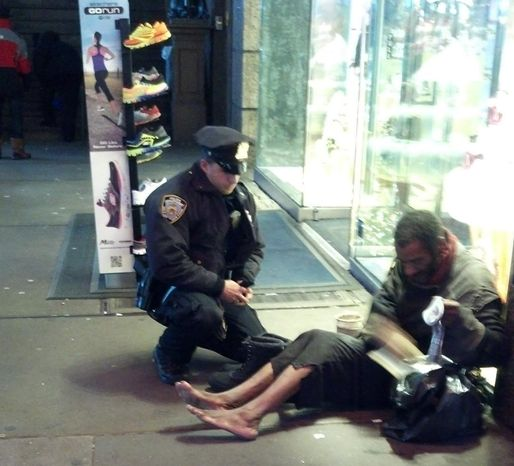 ** FILE ** This file photo provided by Jennifer Foster from Nov. 14, 2012, shows New York City Police Officer Larry DePrimo presenting a barefoot homeless man in New York's Time Square with boots. (AP Photo/Jennifer Foster, File)