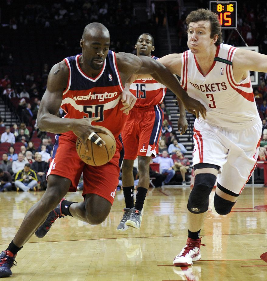 Washington Wizards' Emeka Okafor (50) drives past Houston Rockets' Omer Asik (3) in the first half of an NBA basketball game, Wednesday, Dec. 12, 2012, in Houston. (AP Photo/Pat Sullivan)