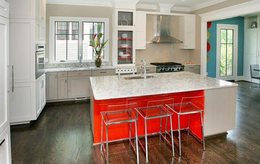 The white-on-white kitchen features a center island, granite counters, two sinks and three dishwashers.