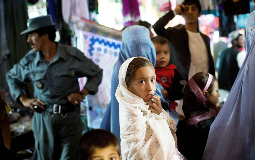 A young Afghan girl shops with her mother in October in a crowded bazaar in the capital of Helmand province, Lashkar Gah. (Associated Press)
