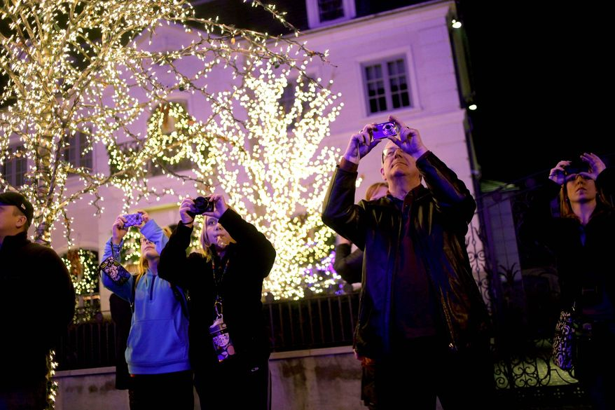 Tourists snap photos as they make their way past holiday displays in the Brooklyn neighborhoods of Dyker Heights and Bay Ridge, where locals take pride in over-the-top displays. (Associated Press)