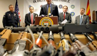 """**FILE** Bill Newell, special agent in charge of ATF Phoenix, speaks Jan. 25, 2011, behind a cache of seized weapons in Phoenix. The ATF is under fire over a Phoenix-based gun-trafficking investigation called """"Fast and Furious,"""" in which agents allowed hundreds of guns into the hands of straw purchasers in hopes of making a bigger case. (Associated Press)"""