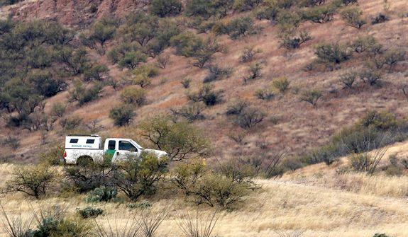 **FILE** A lone U.S. Border Patrol vehicle sits Dec. 16, 2010, in the rugged desert in Rio Rico, Ariz., about 10 miles north of Mexico, as teams of border officers search for the lone outstanding suspect in the fatal shooting of Border Patrol Agent Brian Terry. (Associated Press)