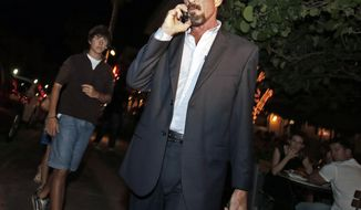 Anti-virus software founder John McAfee talks on his mobile phone as he walks on Ocean Drive in the South Beach area of Miami Beach, Fla., on his way to dinner on Wednesday, Dec 12, 2012. (AP Photo/Alan Diaz)