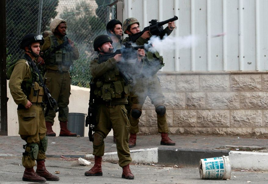 An Israeli soldier shoots a tear gas canister towards Palestinians, not seen, during the funeral Mohammed Suleima, 17, in the West Bank city of Hebron, Thursday, Dec. 13, 2012.  (AP Photo/Nasser Shiyoukhi)