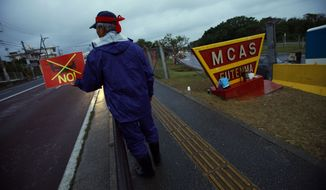 A protester flashes an anti-Osprey placard at a gate of the U.S. Marine Corps Air Station Futenma in Ginowan, Okinawa, in southwestern Japan, on Friday, Nov. 30, 2012. (AP Photo/Junji Kurokawa)