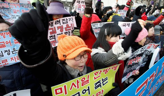 "South Korean housewives shout slogans during a Dec. 13, 2012, rally in Seoul denouncing North Korea's rocket launch. North Korea successfully fired a long-range rocket the previous day, defying international warnings as the regime of Kim Jong Un took a big step forward in its quest to develop a nuclear missile. The letters read ""Denounce North Korea's rocket launch and beat Kim Joung Un."" (Associated Press)"