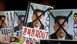 """South Korean protesters hold the pictures of North Korean leader Kim Jong Un during a rally in Seoul on Dec. 12, 2012, denouncing North Korea's rocket launch. The letters read """"Out, Pro-North Korea politic."""" (Associated Press)"""