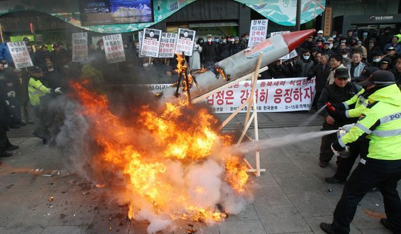 South Korean protesters burn a mock rocket as police officers spray fire extinguishers during a rally in Seoul on Dec. 12, 2012, denouncing North Korea's rocket launch. (Associated Press)