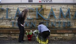 Leslie King, right and Tenille Beseda place flowers Wednesday, Dec. 12, 2012, at the entrance to the scene of a multiple shooting yesterday at Clackamas Town Center Mall in Portland, Ore. A gunman who opened fire on shoppers at the mall had no connection to the two people he fatally shot and wanted to kill as many people as possible, police said Wednesday. (AP Photo/Greg Wahl-Stephens)