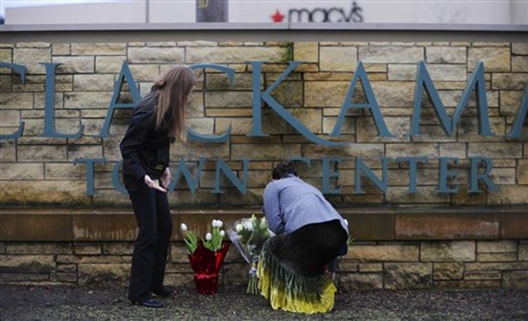 Leslie King, right and Tenille Beseda place flowers Wednesday, Dec. 12, 2012, at the entrance to the scene of a multiple shooting yesterday at Clackamas Town Center Mall in Portland, Ore. A gunman who opened fire on shoppers at the mall had no connection to the two people he fatally shot and wanted to kill as many people as possible, p